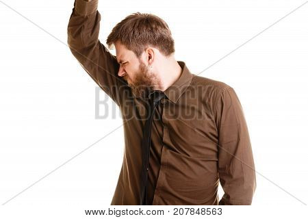 Young brunette man with beard in brown shirt having disgusted look pinching nose cant stand unbearable nasty smell of sweaty garbage or dirty socks isolated on a white background.