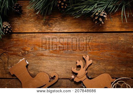Christmas and New Year holiday background. Close up handmade ornaments of skate and deer beneath and pine with strobila above on wooden table, festive decoration concept. Free space in the middle