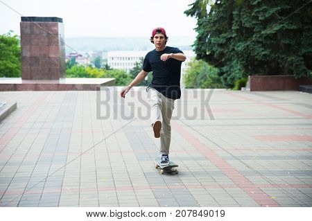 A guy in a cap accelerates pushing his foot on his skateboard on a city park.
