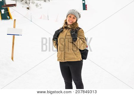 Woman winter hiking. Beautiful young caucasian woman enjoying snow dressed in a cheerful winter cap and with a satchel on her back with copyspace