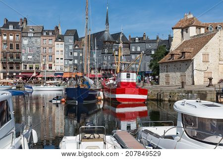 Saling boats and fishing ship in old medieval harbor of Honfleur France