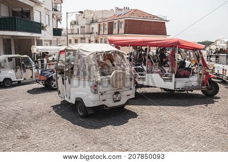 Tuk Tuk Taxi Of Lisbon Stand On A City Square