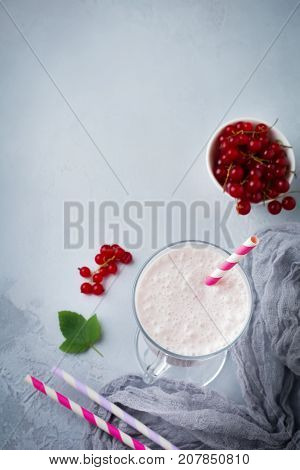 Red currant yoghurt smoothies milkshake in a glass cup on a gray concrete background. Selective focus. Top view.