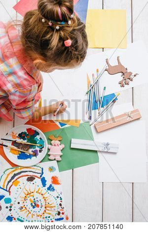 Handmade for kids. Active art childhood. Greeting cards creation, creative baby girl. Early children education top view on wooden background, creativity concept