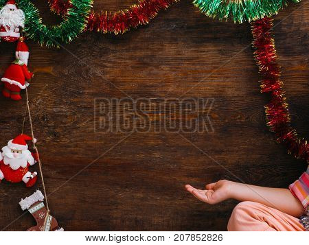 Child waiting for Christmas miracle. Little girl pointing at wooden background with free space. New Year artistic decoration, festivity concept