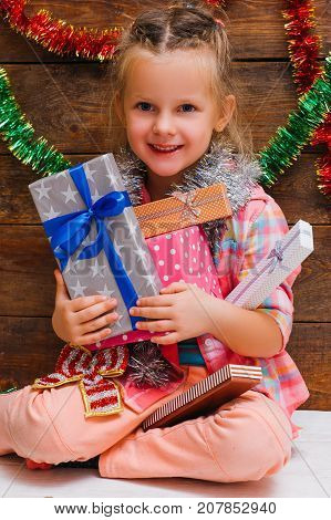 Happy New Year day. Everything for little girl. Many presents for smiley child, christmas miracle. Joyful mood for kid on wooden background, happiness concept