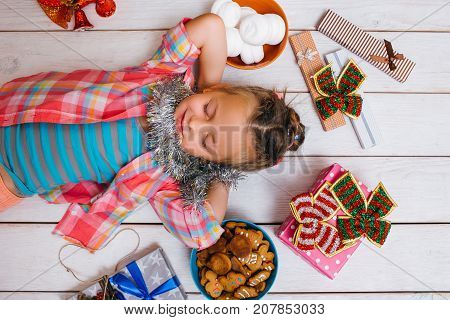 Dream life. Christmas miracle for child. Favorite time of year, joyful girl with tasty sweets on wooden background. Yummy presents. Happiness concept