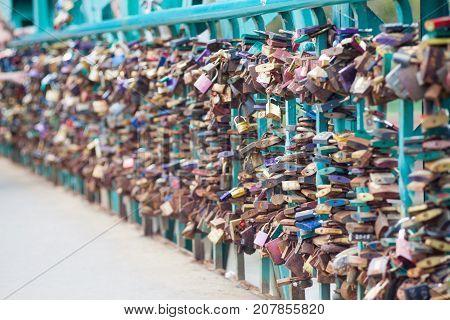 Symbolic love padlocks fixed to the railings of grunwaldzki bridge Wroclaw Poland. Shallow depth of field and creamy bokeh.