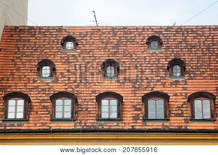 Old Red ceramic Shingles Roof with attic Windows