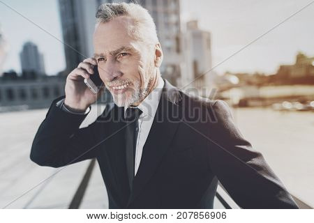 Businessman in a black suit talking on the phone. A broad smile says that the negotiations are proceeding successfully.