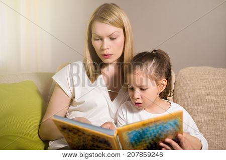 Pretty Beautiful Mother And Her Young Daughter Are Reading A Book.