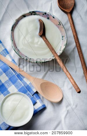 Greek yogurt in a ceramic plate with wooden spoons on a gray concrete background. Selective focus. Rustic style.