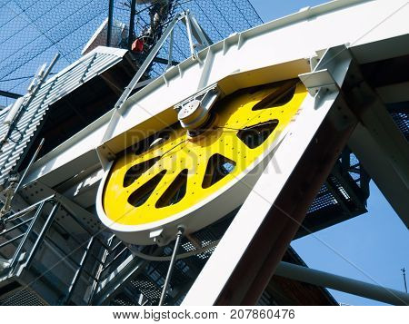 Close-up view of yellow steel giant wheel of cableway.