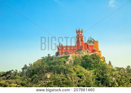 Aerial view of colorful Pena Palace on top of a hill above Sintra in asunny day with blue sky. Panorama of Palacio da Pena, a National Monument, Unesco Heritage and one of Seven Wonders of Portugal.
