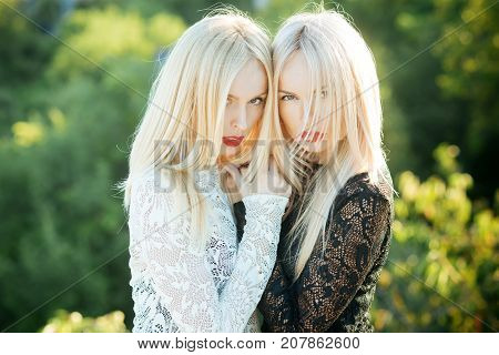 Sisters twins posing on natural landscape. Beauty and fashion. Two women with red lips and long blond hair. Dualism and dualistic nature. Contrasts and opposites concept.
