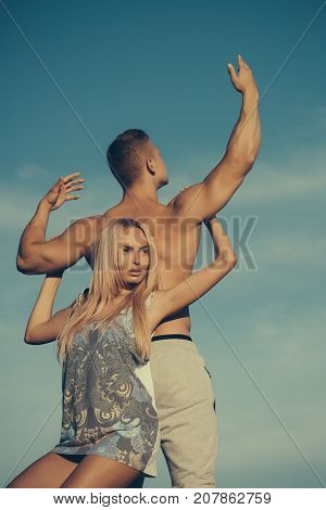 Woman and man holding hands on blue sky. Girl with blond hair and macho with fit torso back. Couple in love on sunny day. Bodybuilding fitness sport and lifestyle. Tenderness and strength concept.