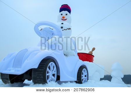 Snowman Driving Toy Car On White Sky
