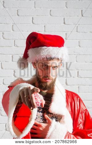 Winter holiday and vacation. Xmas party celebration. Hipster in coat and hat with decoration toy. Christmas man with long beard. New year guy on white brick wall background.