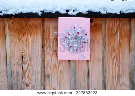 Christmas Present On Snowy Fence On Wooden Background