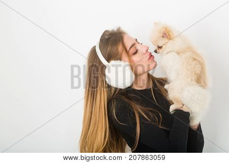 Dog in hand of woman on white background. Girl with happy face in gloves and ears. New year of dog and winter holiday celebration. Woman with small dog of Pomeranian Spitz. Xmas party and vacation.