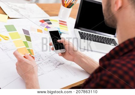 Interior designer working with color palette. Architect choosing colors for building decoration, using mobile phone