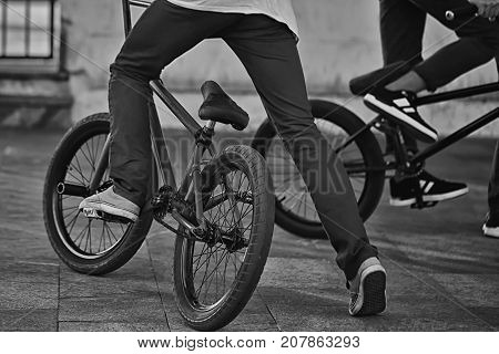 Young teenager bicyclist boy riding on beautiful orange bmx bicycle male hobby extreme sport male hobby lower part closeup on natural background outdoors horizontal picture