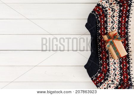 Creative xmas present. Handmade pullover, xmas box on white wood table background. Handmade leisure and winter holidays concept. Copy space, top view