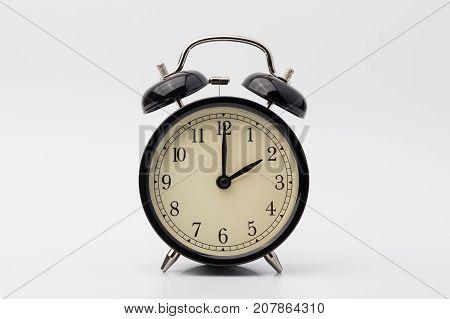 black alarm clock on white background, two o'clock