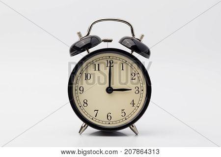 black alarm clock on white background, three o'clock