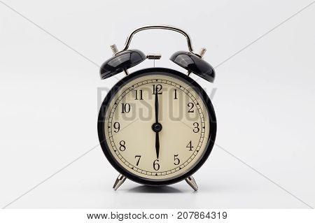 black alarm clock on white background, six o'clock