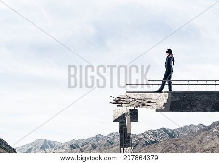 Businessman walking blindfolded on concrete bridge with huge gap as symbol of hidden threats and risks. Skyscape and nature view on background. 3D rendering.
