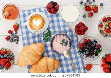 Rich continental breakfast. French crusty croissants, muesli, glass of fresh milk, cup of hot black coffee and lots of sweet berries for tasty morning meals. Delicious start of the day, top view