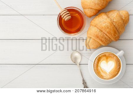 Tasty reakfast background. Hot foamy coffee, honey and fresh croissants on wooden table, top view, copy space. Delicious start of the day and bakery concept