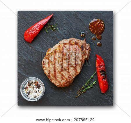 Grilled beef steak and roasted peppers on slate isolated on white background, top view. Juicy meat with rosemary and spices on stone board, restaurant food