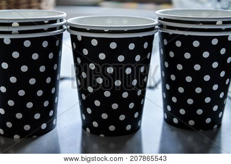 Paper cups in black and white polka dots. Disposable paper cup for coffee and hot drinks.