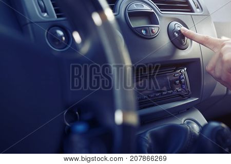 The passenger in the car presses the button climate control