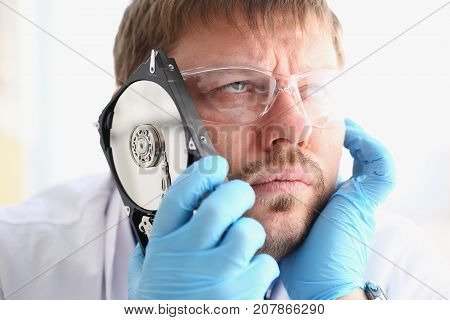 Repairman attached the hard drive of the computer to his ear. Listens to knock and crack reveals the problematic problems and ringing affecting correct operation of hard drive, tests and repairs.