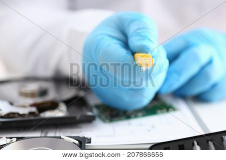 A male hand in blue protective gloves holds a network connector. The LAN constructor deconstructs the connection of clients to the Internet on the basis of xpon and Adsl