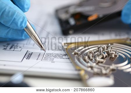 A male hand in protective blue gloves holds a pen in his hand and shines with electronic circuitry. Small bolts removed macro in repair shop to restore micro-engineering background