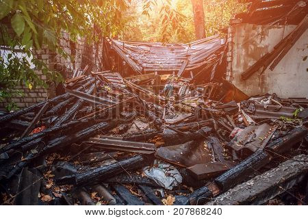 Burned house, debris and ruins of destroyed building by fire, ash and coal, arson concept, toned