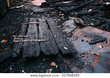 Charred wooden door of burnt house, Burned ruins of destroyed building by fire, ash and coal, arson concept