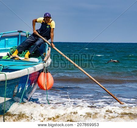 Man Pushes Against Sand To Release Boat From The Surf In Puerto Lopez, Ecuador