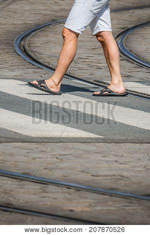 Man in flip flops crossing the road in town in summer