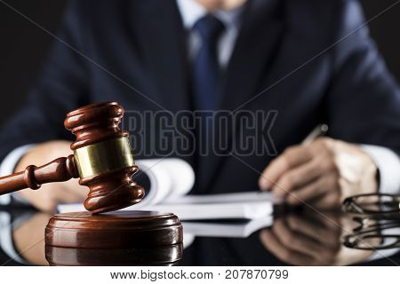 Legal advice concept. Man signing documents. Gavel.