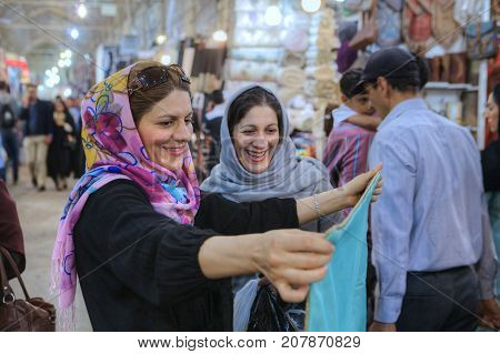 Fars Province Shiraz Iran - 19 april 2017: Two smiling Muslim women in colored hijab choose fabric to buy at the Vakil Grand Bazaar.
