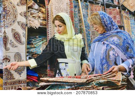 Fars Province Shiraz Iran - 19 april 2017: Two fashionable Iranian women young and mature dressed in bright colorful head scarves choose the item to the carpet shop in the central basaar.