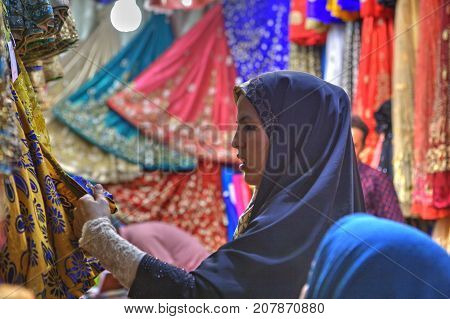 Fars Province Shiraz Iran - 19 april 2017: One young Iranian woman wearing in hijab choose the fabric for purchase in a textile shop in the bazaar.