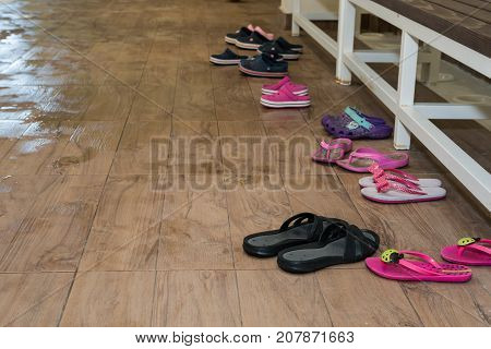 Children flip flops on the wooden background by swimming pool