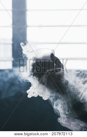 Creative alcoholic cold drink with white smoke. Glass with liquid in focus on foreground, bad habits addiction, unrecognizable male, dark atmosphere background