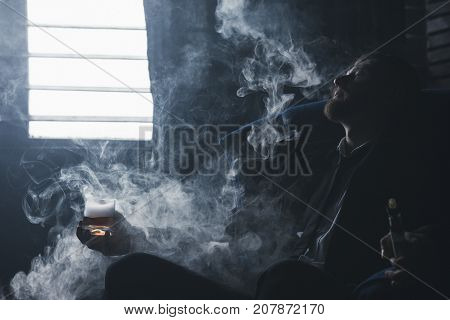 Problems in life. Career crash. Successful man lost everything, despair in alcohol and vaping. Tired bankrupt, depressed guy in smoke in dark room, bankruptcy concept
